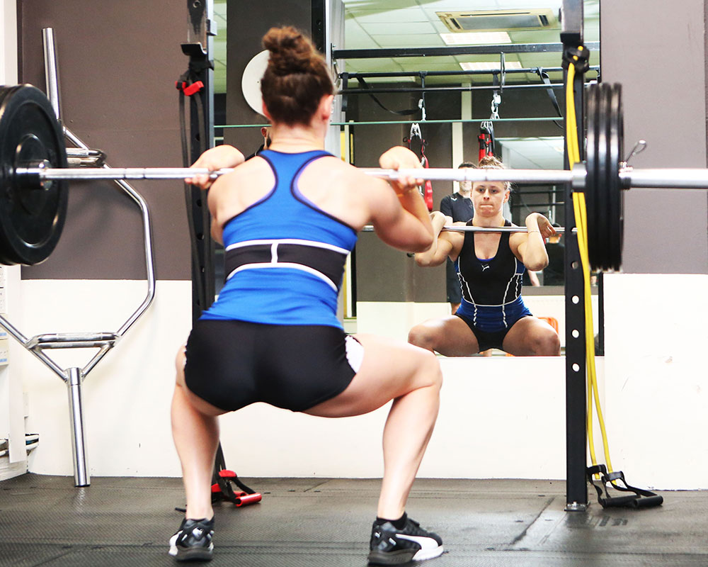 International athlete Sinead Denny, performs a squat with barbell